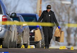A crime lab investigator carries bags of evidence past…