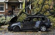 A man sits on his porch behind a car that was burned out in an electrical fire after a tree fell over a power line due to the remnants of Hurricane Sandy in Toronto, October 30, 2012. REUTERS/Mark Blinch