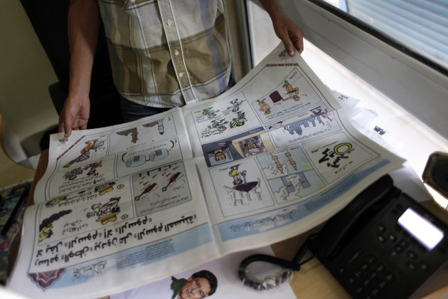 """Egyptian cartoonist Khalid Abdul-Ati holds a copy of the Egyptian Al Watan daily newspaper with a two-page spread of cartoons with a headline in Arabic that reads """"nothing cracks cartoons but cartoons,"""" inside his office at the newspaper's headquarters in Cairo, Egypt, Wednesday, Sept. 26, 2012. Amid outrage sparked by perceived insults to Islam, one Egyptian newspaper has decided to fight cartoons with cartoons. Al Watan daily says it is responding to the crude caricatures published last week by a satirical Parisian weekly in kind: a series of sketches critiquing relations between the Arab world and the West. The paper says they are a """"civilized"""" alternative to the violent protests across the Muslim world sparked by a low-budget anti-Islam film produced in the United States. (AP Photo/Nasser Nasser)"""