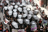 Journalists carry mock coffins and pictures of massacred colleagues while marching to Mendiola in Manila yesterday to commemorate the third anniversary of the killing of 58 people, including 33 journalists in Maguindanao. <b>EDD GUMBAN                                                                                                                                                               </b>