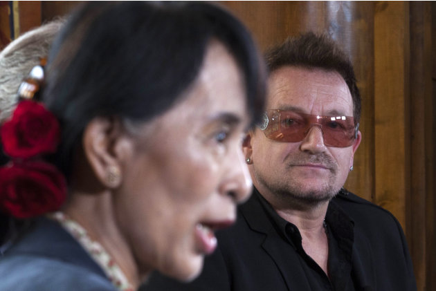 Irish singer and activist Bono, right, looks on as Myanmar's opposition leader Aung San Suu Kyi, left, speaks during a news conference after attending a conference of the Oslo Forum at the Losby Gods