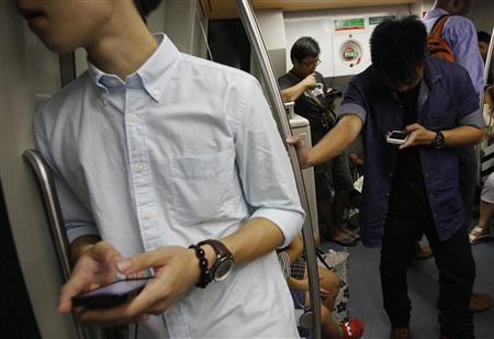 Commuters use their smartphones in a train in Singapore January 26, 2013. REUTERS/Edgar Su