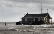 A man walks away from a building that has been surrounded by water pushed up by Hurricane Sandy in Bellport, New York, October 30, 2012. REUTERS/Lucas Jackson
