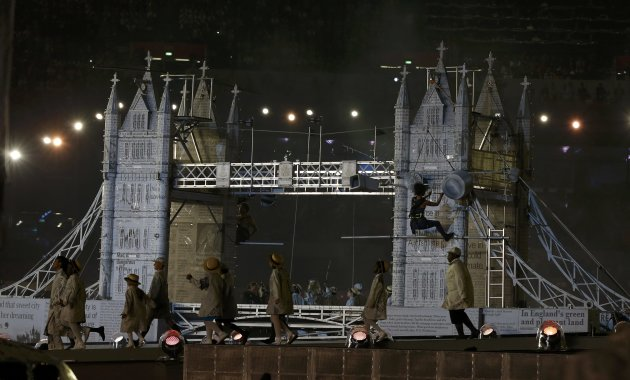 Performers walk by a model of Tower Bridge during the closing ceremony of the London 2012 Olympic Games at the Olympic Stadium