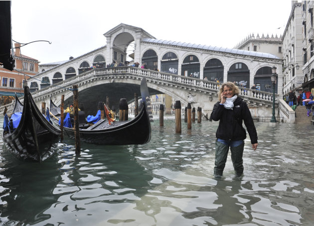 A woman walks in high water ner the Rialto Bridge in Venice, Italy, Thursday, Nov. 1, 2012. High tides have flooded Venice, leading Venetians and tourists to don high boots and use wooden walkways to