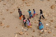 Indian villagers cross a dry river bed in Gandhinagar district. With drought parching farms in the United States and near the Black Sea, weak monsoon rains in India and insidious hunger in Africa's Sahel region, the world could be headed towards another food crisis, experts say