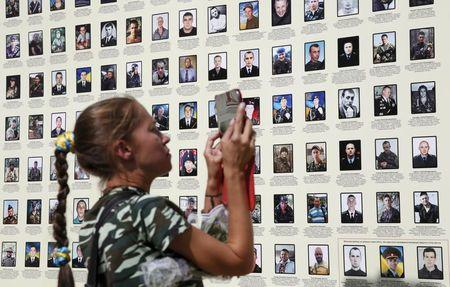 Woman uses her tablet at wall with portraits of Ukrainian servicemen killed year ago during fights with pro-Russian rebels near Ilovaysk, during a...