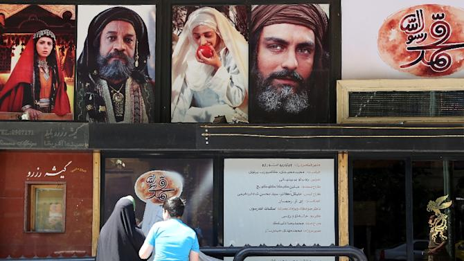 "Iranians stand in front of a cinema featuring ""Muhammad"" in Tehran on August 27, 2015 -- the first day of screening"