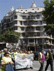 """Protesters from the """"Yayoflautas"""" movement hold a banner as they march past the Casa Mila, designed by Catalan architect Antoni Gaudi, in central Barcelona June 22, 2012. REUTERS/Gustau Nacarino"""