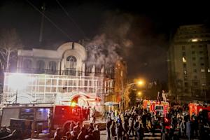 Smoke rises as Iranian protesters set fire to the Saudi …