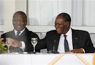 Ivory Coast's President Alassane Ouattara (R) smiles next to Interior Minister Hamed Bakayoko during a news conference in Man, in the west of Ivory Coast April 24, 2012. REUTERS/Thierry Gouegnon