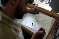 """Egyptian cartoonist Khalid Abdul-Ati from the Egyptian Al Watan daily newspaper works on a cartoon depicting an Islamic figure inside his office at the newspaper's headquarters in Cairo, Egypt, Wednesday, Sept. 26, 2012. Amid outrage sparked by perceived insults to Islam, one Egyptian newspaper has decided to fight cartoons with cartoons. Al Watan daily says it is responding to the crude caricatures published last week by a satirical Parisian weekly in kind: a series of sketches critiquing relations between the Arab world and the West. The paper says they are a """"civilized"""" alternative to the violent protests across the Muslim world sparked by a low-budget anti-Islam film produced in the United States. (AP Photo/Nasser Nasser)"""
