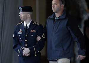 Army Pfc. Bradley Manning, left, is escorted to a security…
