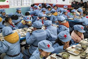 Children dressed in uniforms eat their lunch at the …