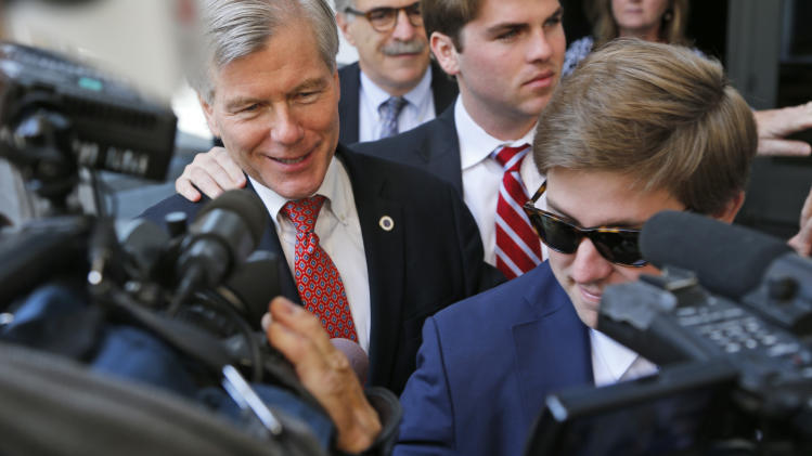 Former Virginia Gov. Bob McDonnell, left, is swarmed by the media as he leaves Federal Court for the third day of jury deliberations in his corruption trial in Richmond, Va., Thursday, Sept. 4, 2014. McDonnell and his wife Maureen are charged in a 14-count indictment with doing special favors for Jonnie Williams, the CEO of dietary supplements maker Star Scientific Inc., in exchange for $165,000 in gifts and loans. (AP Photo/Steve Helber)