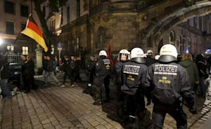 Riot police separate people holding a German flag and …
