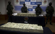 """Mexican army soldiers stand by the more than $15 mn in cash that was seized on November 18 during the regional """"Operation Fox"""" in Tijuana. (AFP Photo/Yuri Cortez)"""