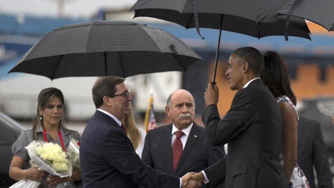 President Barack Obama, right, shakes hands with Cuba's Foreign Minister Bruno Rodriguez as first lady Michelle Obama stands behind, right, upon arrival to the airport in Havana, Cuba, Sunday, March 20, 2016. Obama's trip is a crowning moment in his and Cuban President Raul Castro's ambitious effort to restore normal relations between their countries. (Cubadebate/Ismael Francisco via AP)