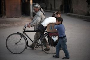 A Syrian man and his children carry sacks of aid provided...