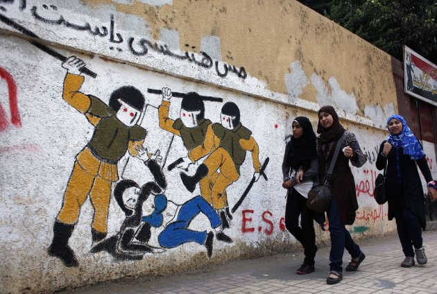 """In this Thursday, Oct. 4, 2012 photo, Egyptian girls walk past a mural inspired by a widely circulated photo of Egyptian police beating and stripping a veiled female protester, on a recently whitewashed wall with Arabic that reads """"we will not forget you our lady,"""" in Tahrir Square, Cairo, Egypt. Graffiti has been among the most powerful art forms and tools of Egypt's revolution and the turbulent months since, but it also has proven to be its most vulnerable and ephemeral. So a group of artists, photographers and a publisher joined hands to preserve the images. """"Wall Talk"""" _ their newly released, 680-page book _ collects hundreds of photos of graffiti dating from the Jan. 25, 2011 eruption of the revolt against then-President Hosni Mubarak until today. (AP Photo/Nasser Nasser, File)"""