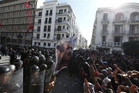 Tunisian protesters clash with riot police during a demonstration after the death of Tunisian opposition leader Chokri Belaid (in poster), outside the Interior ministry in Tunis February 6, 2013. REUTERS/Anis Mili