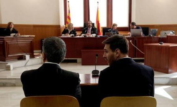 Barcelona's Argentine soccer player Lionel Messi sits in court with his father Jorge Horacio Messi during their trial for tax fraud in Barcelona