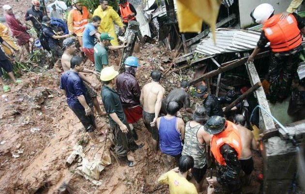 Rescue workers dig through mud in search for survivors in a landslide incident that struck Litex, Barangay Commonwealth in Quezon City, northeast of Manila, Philippines, on Tuesday Aug. 7, 2012.