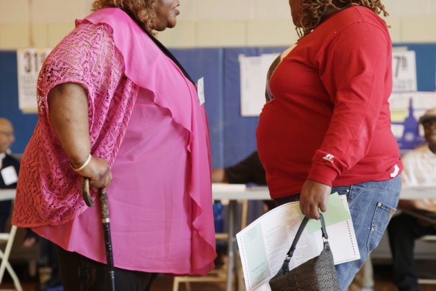 In this June 26, 2012, photo, two overweight women hold a conversation in New York. A new poll suggests that while more than 7 in 10 Americans can correctly tick off heart disease and diabetes as obesity's most serious consequences, few Americans are aware of the lesser-known health consequences_ such as worsening some types of cancer, arthritis, sleep apnea and even infertility. Only about one-quarter of people think it's possible for someone to be very overweight and still healthy, according to the poll by The Associated Press-NORC Center for Public Affairs Research. (AP Photo/Mark Lennihan)
