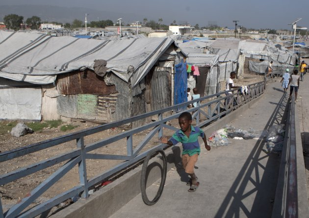 In this Wednesday, June 13, 2012 photo, a boy rolls a bicycle tire up a ramp near a camp for people displaced by the 2010 earthquake in Port-au-Prince, Haiti. Amid the horrors of Haiti's 2010 earthqua