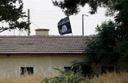 File photo of an Islamic State flag flying over the customs office of Syria's Jarablus border gate as it is pictured from the Turkish town of...