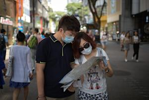 Tourists wearing face masks look at a map in the popular …