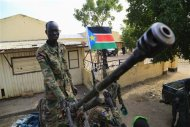 A South Sudan army soldier stands next to a machine gun mounted on a truck in Malakal town, 497km (308 miles) northeast of capital Juba, December 30, 2013 after retaking the town from rebel fighters. REUTERS/James Akena