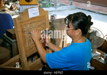 Thailand A Thai Woman Carving Wood In A Workshop Near
