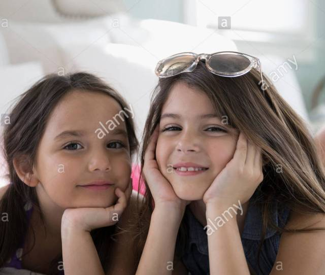 Portrait Smiling Latina Sisters Laying On Bed