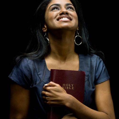 Femme tenant une bible dans ses bras et regardant Dieu