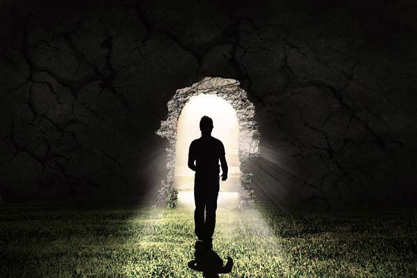 Homme dans l'ombre marchant vers la lumière