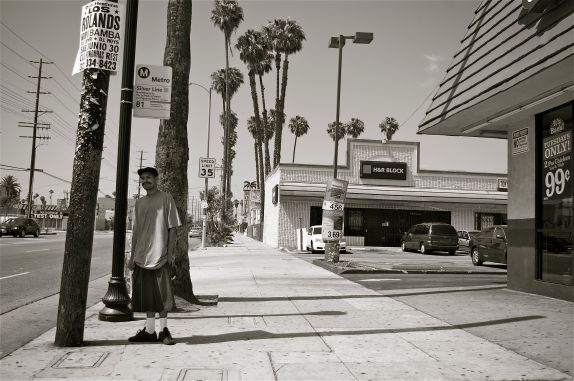 A man waits for a bus in the shade of a telephone pole on Figueroa Ave., just north of 85th St. There tends to be fewer shelters and less shade available to those who are most heavily dependent on transit. Sahra Sulaiman/Streetsblog L.A.