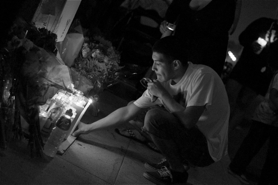 Jose Vasquez leaves a candle at the ghost bike memorial for Andy Garcia, killed last week in a vicious hit-and-run.  Sahra Sulaiman/LA Streetsblog