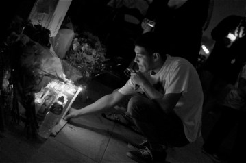 Jose Vasquez leaves a candle at the ghost bike memorial for Andy Garcia, killed in a vicious hit-and-run last year.  Sahra Sulaiman/LA Streetsblog