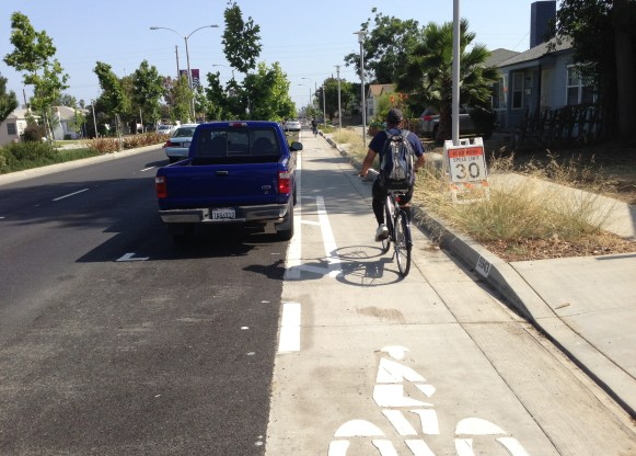 Similar on-street parking as the above image, but shown with parked car. These parked cars also provide protection between the bikeway and the street travel lanes.