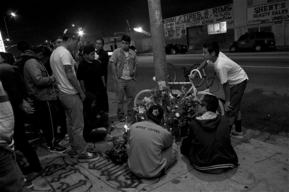 Friends of Oscar Toledo, Jr., gather around the ghost bike put up at 47th and Normandie in South LA. Sahra Sulaiman/Streetsblog LA