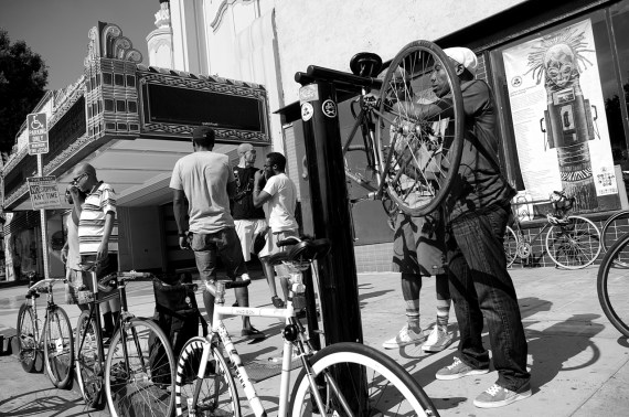 Ade Falade puts his bike up on the stand at the repair station outside the KAOS Network in Leimert Park as members of Black Kids on Bikes gather for their monthly ride. Sahra Sulaiman/Streetsblog L.A.