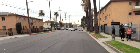 Preliminary striping on Venice Boulevard at Wilton. Cyclists and pedestrians compete for sidewalk space, while cars get four lanes and parking.