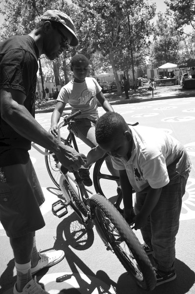 Jeremy Swift teaches the boy to work on his bike while Cortez Wright watches. Sahra Sulaiman/Streetsblog L.A.