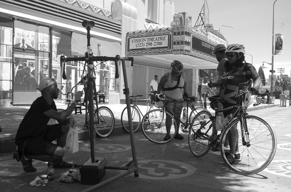 Erik Charlot works on a bike while chatting with some of the lovely ladies of Major Motion. Sahra Sulaiman/Streetsblog L.A.
