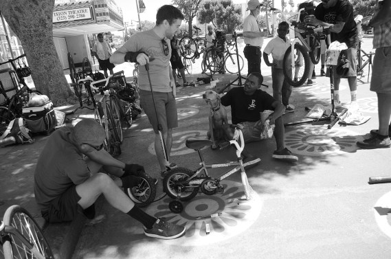 Michael Glasco, Michael MacDonald, dog Tobey, and Malik Mack make sure a tiny bike is in working order. Sahra Sulaiman/Streetsblog L.A.