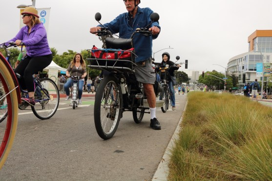 Bicyclists pass by city hall and Tongva Park.