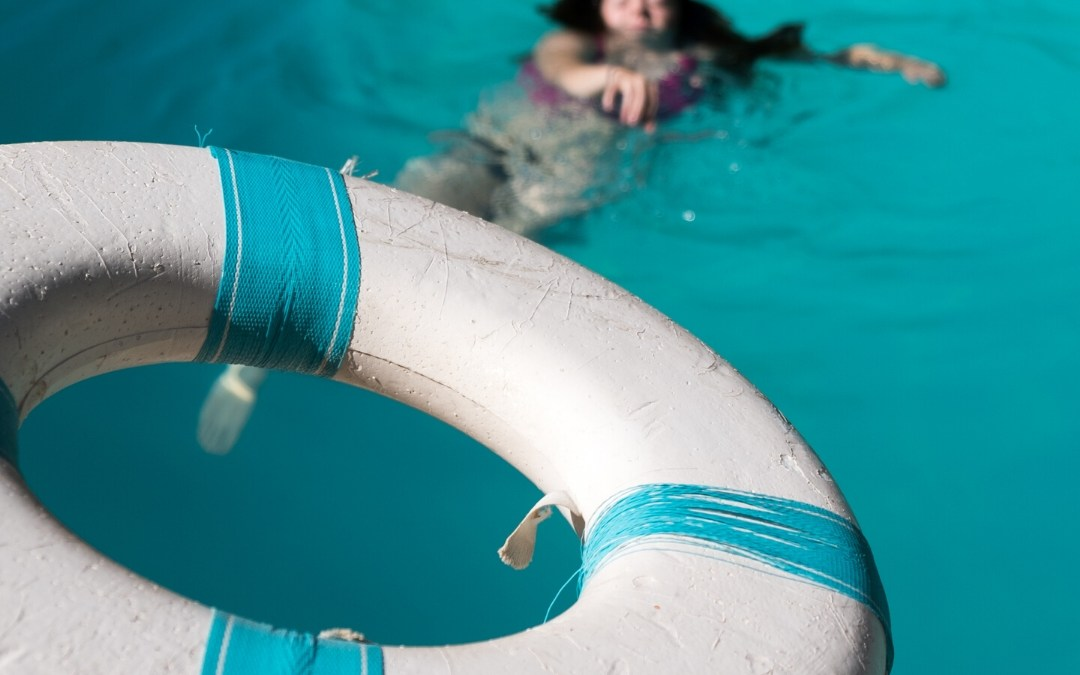 Pessoa se afogando com bóia salva-vidas em uma analogia com proteção financeira