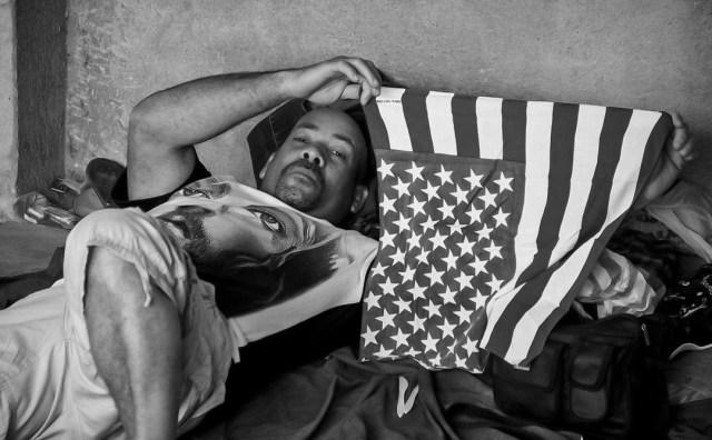 Adalberto sostiene una bandera estadounidense mientras descansa en un alojamiento para refugiados en La Cruz.