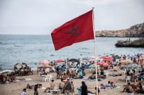 Playa de Carabonita con una gran bandera de Marruecos en medio de la arena. Alhucemas es una ciudad turística, y mientras se suceden las protestas, mucha gente disfruta del mar. Los jóvenes activistas usan también las orillas para denunciar la situación y suelen juntarse en grupos para gritar a favor de las reivindicaciones sociales.